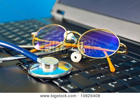 Stethoscope and glasses on black laptop