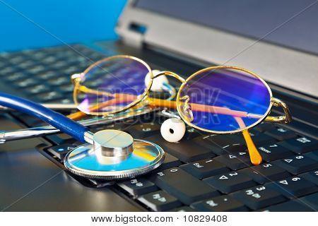 Estetoscópio e óculos no laptop preta