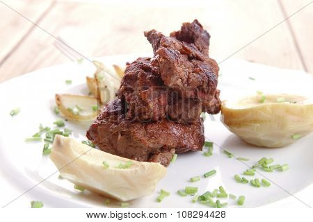 beef bourguignon in wine with artichoke and marinated vegetables on white plate over wooden table
