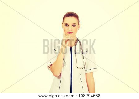 Beautiful pensive female doctor with hand on chin.