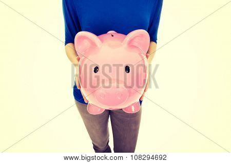 Casual woman holding a piggybank.