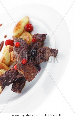 grilled beef meat with berries fried potatoes and cherry under sweet honey sauce on white plate isolated over white background