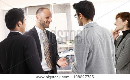 Corporate businesspeople talking in front of meeting room, smiling.
