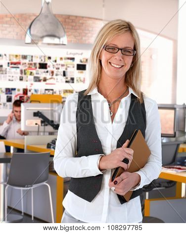 Happy blonde caucasian casual mid adult businesswoman standing at office, wearing glasses, smiling, looking at camera with personal organizer in hand.