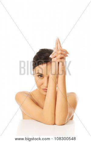Topless woman doing gun sign by hands.