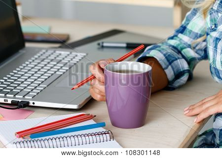 Female Designer Hands Holding Cup Of Hot Beverage And Drawing With Pencil