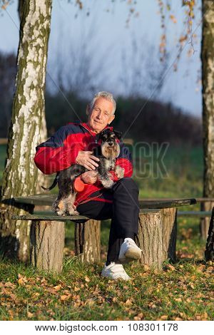 Senior Man With Dog In The Park