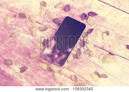 Blank Cell Phone Screen On Wooden Table With Leaves, Instagram Photo Effect