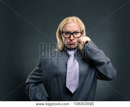 Funny nerd businesswoman in glasses over grey background