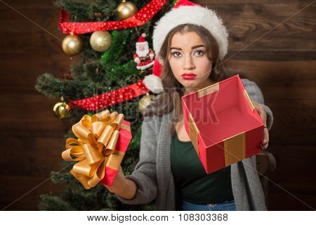 Beautiful girl demonstrating empty box of present near New Year tree