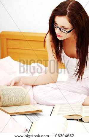 Woman is note something from the books in bed. Working or studing concept.
