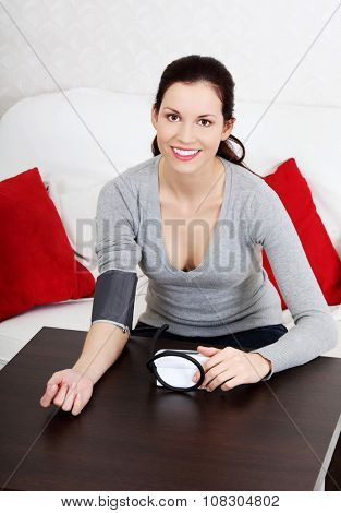 Beautiful woman is measuring her blood pressure. Ilness concept.