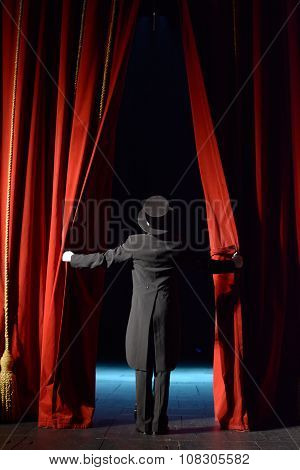 actor in a black tuxedo opens red theater curtain