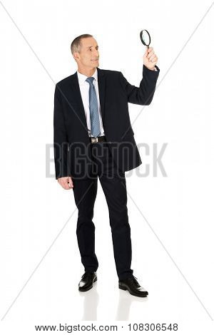 Full length businessman with a magnifying glass.