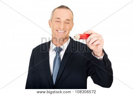 Mature businessman writing with an oversized red pencil.