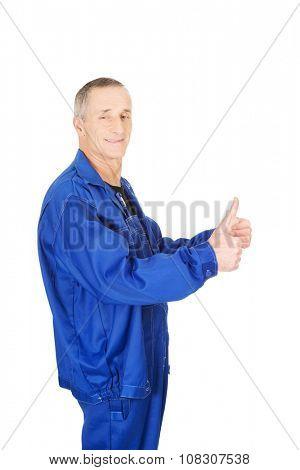Mature repairman showing thumbs up.