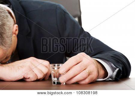 Overworked mature man drinking vodka in office.
