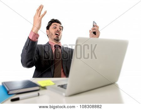 Attractive Businessman Sitting At Office Desk Working In Stress On Computer Laptop Talking On Mobile