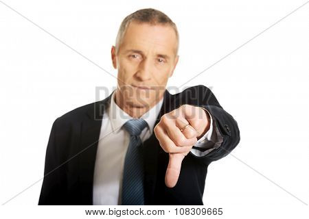 Portrait of businessman showing thumb down sign.