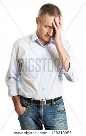 Depressed mature man touching his head.