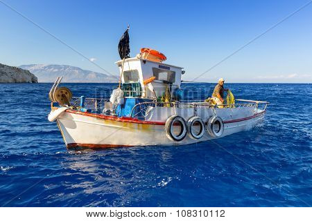 ZAKYNTHOS, GREECE - AUG 22, 2015: Fisherman on the boat at the Blue caves of Zakynthos island, Greece. Sunrays reflect through blue sea water from white limestones creating visual lighting effects.
