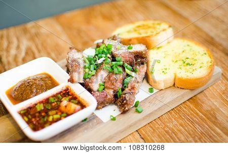 Slice Grilled Pork With Thai Chilli Sauce And Garlic Bread Serve On Chopping Block On Wood Table