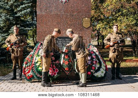Unidentified re-enactors dressed as Soviet soldiers laying of wr