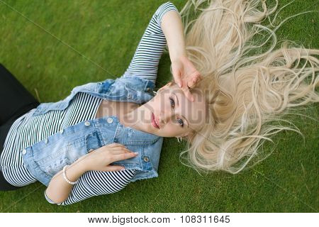 Blonde Woman Lying On The Grass With Untressed Hair