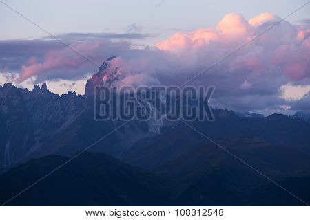 Mountain landscape. Peak of the mountain in the clouds. Beautiful sunset with clouds. Mountain Ushba, Caucasus, Georgia, Zemo Svaneti