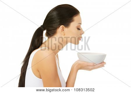 Beautiful young woman holding bowl and smells