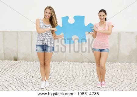 Two beautiful teenage students holding a giant puzzle piece