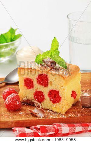 Raspberry sponge cake slice on a wooden cutting board