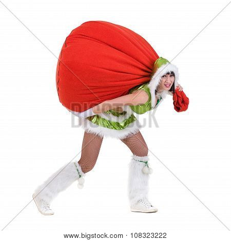 Woman dressed like a funny gnome pulls red bag with gifts, isolated on white