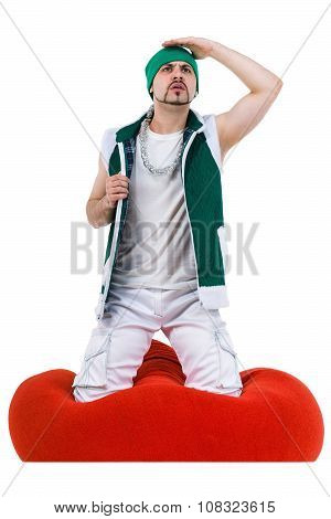 Surprised man dressed like a gnome sitting on red bag with gifts, isolated over white