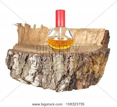 Perfume Bottles With Red Cover On A Piece Of Birch Trunk Isolated On White Background.