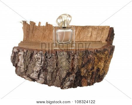 Empty Bottle Of Perfume On A Piece Of Birch Trunk Isolated On White Background.