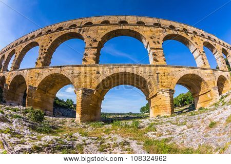 Three-tiered aqueduct bridge Pont du Gard was built in Roman times on the river Gardon. Provence sunset. Photo taken fisheye lens