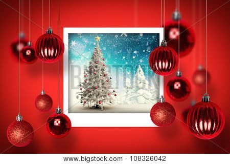 Christmas tree in snowy landscape against christmas photographs