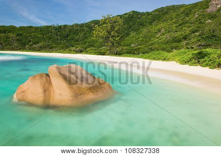Beautifully shaped granite boulder in the turquoise sea (daytime long exposure technique) and a perfect white sand at Anse Coco, La Digue island, Seychelles