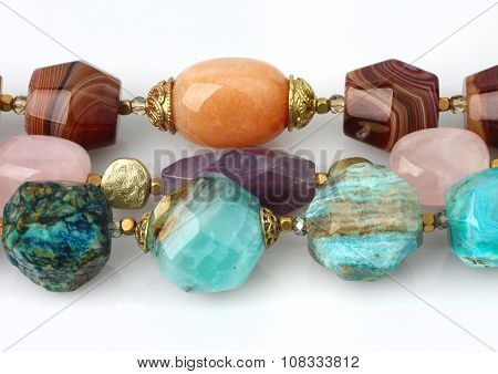 Close-up Of Colorful Natural Precious Gems Jewelry On White