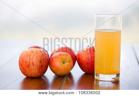 apples and juice on a wooden table, outdoor