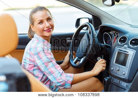 Young Beautiful Woman Sitting In A Convertible And Is Going To Start The Engine