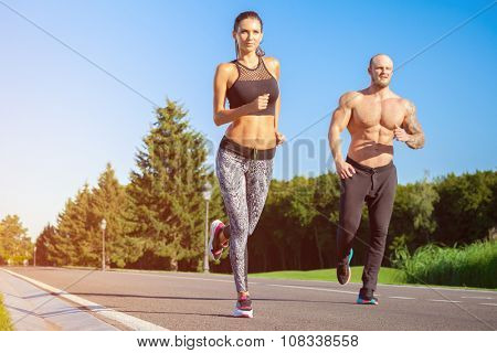 Young strong male and female  fitness models outdoors in beautiful landscape. Man and woman running in park at sunset