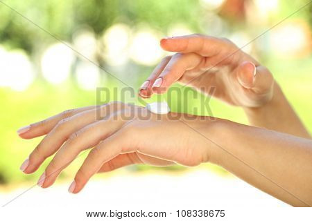 Nutritive hand cream on female's arm outdoors on blurred background