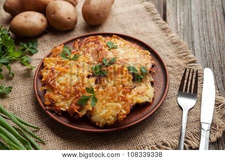 Homemade traditional potato pancakes or latke Hanukkah celebration food in rustic clay dish on vinta
