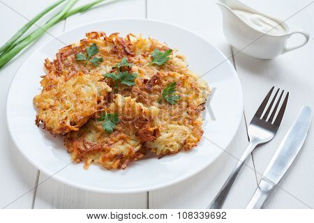 Fried potato pancakes or latke traditional homemade Hanukkah celebration food with greens and sour c
