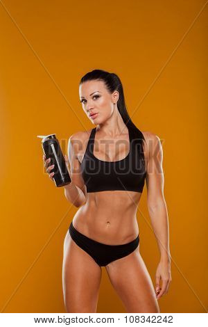 Sporty muscular  woman with water, isolated yellow background