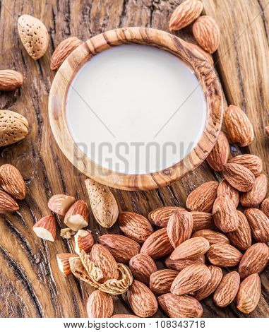 Almond nuts and milk on wooden table.