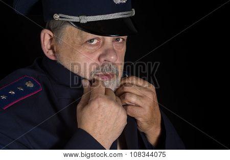 Portrait of older man in police uniform in low key