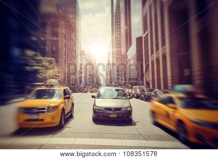 NEW YORK - SEPTEMBER 06: Front View of Sedan Driving on Urban City Street Between Two Speeding Yellow Taxi Cabs with Bright Sun Shining in Background  in New York City, USA. September 06 2015.
